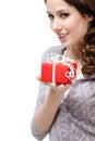 Den gåtfulla unga kvinnan räcker en gåva som slås i rött pappers isolerat på vit Royaltyfri Foto