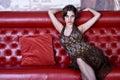 Den trevliga flickan sitter sofaen Fotografering för Bildbyråer