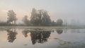 Dense fog at sunrise on pond. Trees reflecting in water Royalty Free Stock Photo