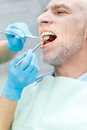 Dentist curing mature patient in dental clinic