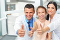 Dentist doctor,  assistant and little girl all smiling at camera Royalty Free Stock Photo