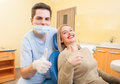Dentist doctor and patient showing thumbs up