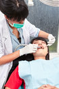 Dentist examing teeth young female doing examination on her patient Stock Images
