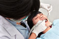 Dentist examing teeth young female doing examination on her patient Royalty Free Stock Photography