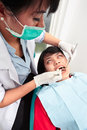 Dentist examing teeth young female doing examination on her patient Stock Photo
