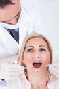 Dentist examining patient male female in clinic Stock Photos
