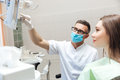 Dentist explaining x ray picture to patient on LED monitor Royalty Free Stock Photo
