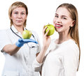 Dentist giving apple fruit to young woman. Royalty Free Stock Photo