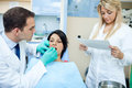 Dentist and a nurse with patient in office curing teeth of female Royalty Free Stock Photography