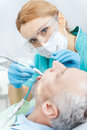 Dentist in protective glasses and mask curing mature patient