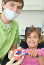 Dentist shows to patient girl how to brush teeth Stock Photography