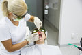 Dentist using a modern diode dental laser for periodontal care both wearing protective glasses preventing eyesight damage Royalty Free Stock Photos