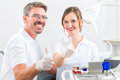 Dentists in their surgery or office with dental tools successful looking at the viewer standing side by side Royalty Free Stock Photo