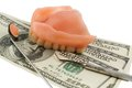 Dentures and dollar bills symbol photo for treatment costs payment Stock Photos