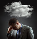 Depressed businesman stress depression and despair gloomy storm cloud raining above a businesmans head Stock Image