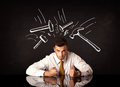 Depressed businessman sitting under hammer marks Royalty Free Stock Photo