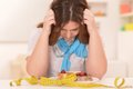 Depressed dieting woman with cake and measuring tape Stock Photos