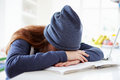 Depressed girl studying at home with head in arms unhappy Royalty Free Stock Photography
