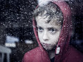 Depressed little boy sad looking through window at rainy weather can t play Royalty Free Stock Image