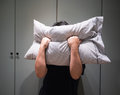 Depressed man covering his face with pillow and screaming in anger Royalty Free Stock Photo