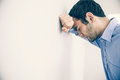 Depressed man leaning his head against a wall Royalty Free Stock Photo