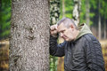 Depressed man leaning on a tree in forest Stock Image
