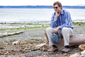 Depressed man sitting on driftwood on beach sad caucasian in forties chin in hand Royalty Free Stock Photography