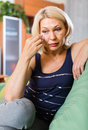 Depressed mature woman on sofa at home Stock Photo