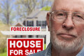 Depressed Senior Man in Front of Foreclosure Sign and House Royalty Free Stock Photo