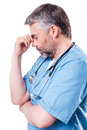 Depressed surgeon side view of mature doctor touching his face with hand and keeping eyes closed while standing isolated on white Stock Photo