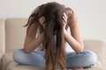 Depressed teenager having problems, stressed woman holding head