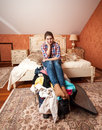 Depressed woman sitting on unpacked suitcase portrait of at bedroom Stock Photos