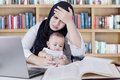 Depressed woman working with baby in library Royalty Free Stock Photo