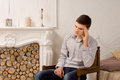 Depressed young man sitting thinking handsome stylish in an old wooden chair in front of a marble fireplace with his head on his Stock Images