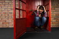 Depressed young woman sitting in a phone booth Royalty Free Stock Photo