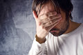 Depressive man is crying with hand covering his face looking upset and showing remorse Royalty Free Stock Images