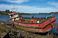 Derelict boat fishing stranded on the shore in castro capital of chiloe island in chile Royalty Free Stock Images