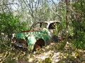 Derelict car in forest abandoned a Stock Photos