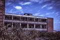 Derelict red brick office building under a blue sky Royalty Free Stock Photo