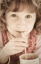 Desaturated image of oung girl with curly red hair drinking through a straw old fashioned looking de saturated preschool aged Stock Photography