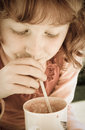 Desaturated image of oung girl with curly red hair drinking through a straw old fashioned looking de saturated preschool aged Royalty Free Stock Photography