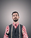 Desaturated portrait of young bearded hipster with hands pushed in his vest over dark gray studio background vignette Royalty Free Stock Photos