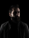 Desaturated serious bearded hipster looking away high contrast low key dark shadow portrait isolated over black background Royalty Free Stock Photos