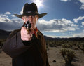 Desert gunfight cowboy pointing gun with selective focus on gun against background Royalty Free Stock Photos
