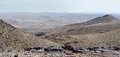Desert landscape on hazy day with far bedouin camp Royalty Free Stock Image