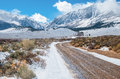Desert mountain road in winter a dirt wet with melting snow leads across a plain toward the sierra nevada mountains near yosemite Stock Images