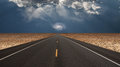 Desert road leads into toward galaxy above horizon Royalty Free Stock Images
