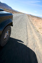 Desert travelling a four wheel drive car on a road in morocco Stock Image