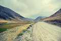 Desert tundra high mountain river valley with dusty road Royalty Free Stock Photo
