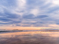 Deserted beach sunset sky reflected wet sand Stock Photo